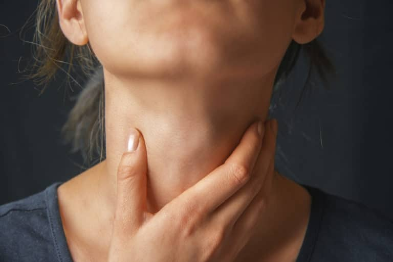 A person tipping their chin up and holding their throat