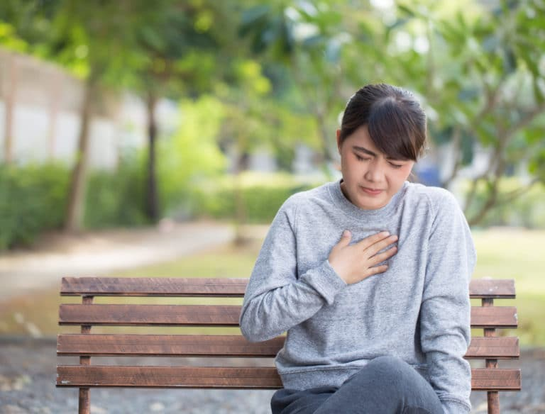 A person sitting on a bench and holding their chest in pain