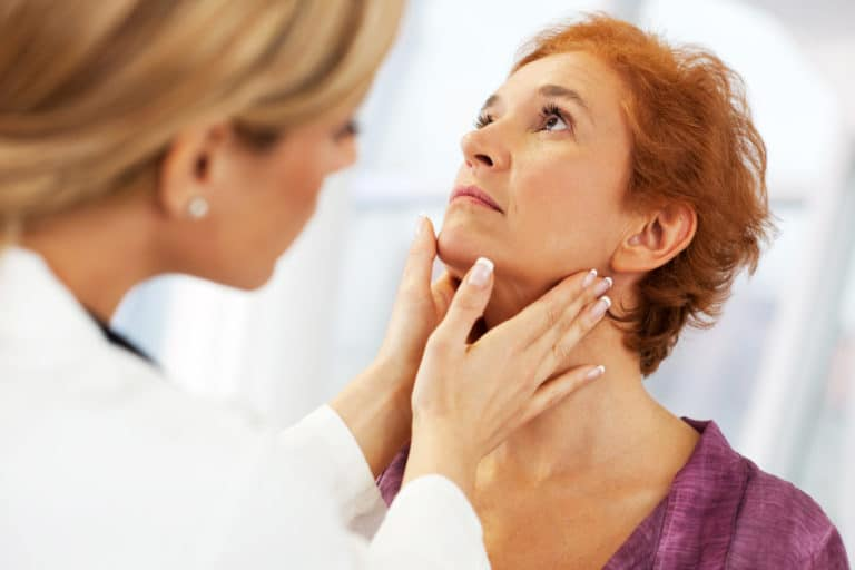 A patient having their throat examined by touch