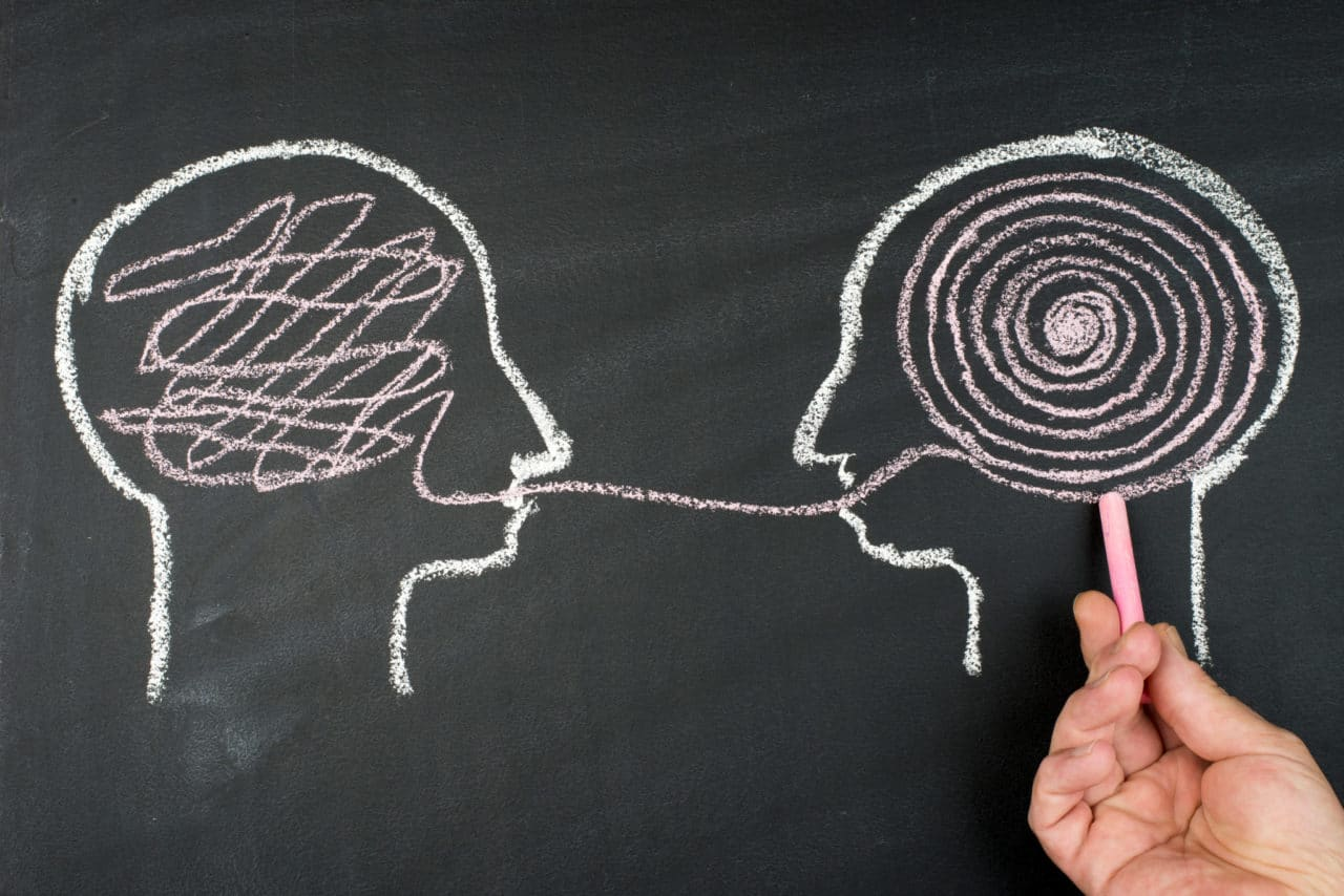 A chalk drawing of two human head profiles facing each other with thoughts visualized as a spiral in one head and a scribble in the other, both connected by a single line through the mouths
