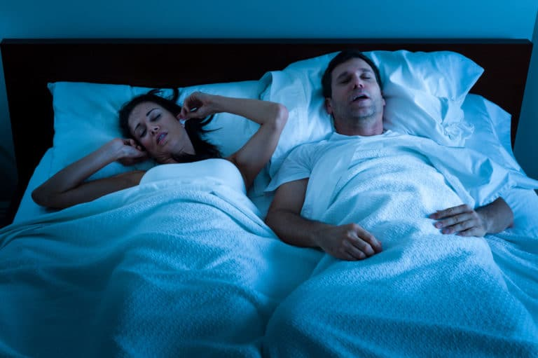 Two people in a bed, one holding their ears in frustration as the other snores