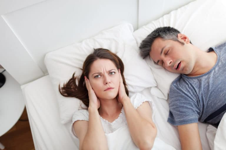 A person covering their ears in annoyance while another person sleeps soundly (presumably snoring) next to them
