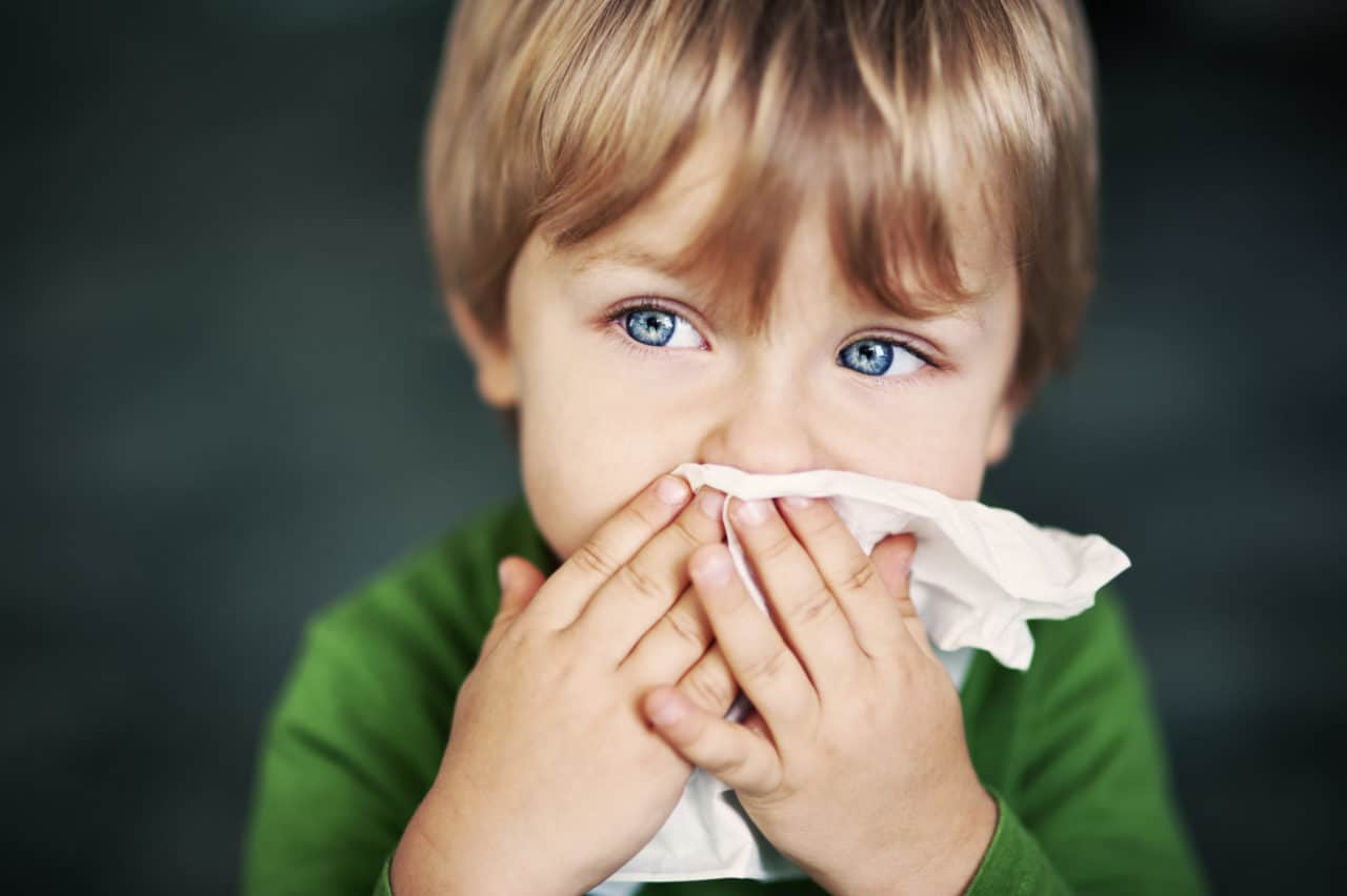 A child wiping their nose with a tissue