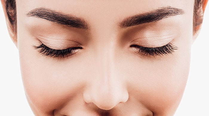 A close-up of a person looking down and wearing mascara and metallic eyeshadow