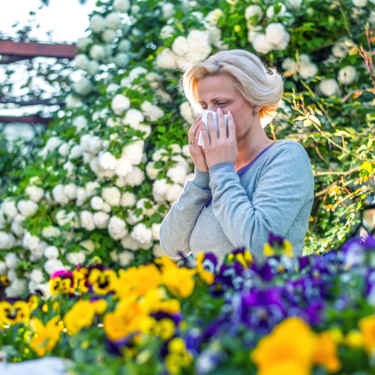 Woman covering sneeze in garden