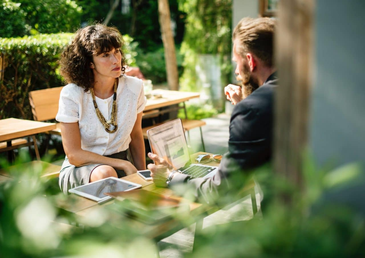 man and woman sitting at a table in a garden having a discussion