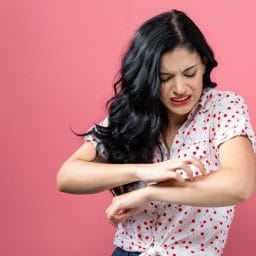 Young woman scratching her itchy arm.