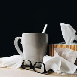 A mug, some tissues and a pair of glasses.