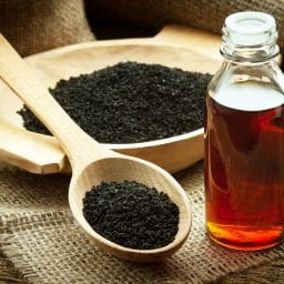 Black cumin on wooden spoon and essential oil.